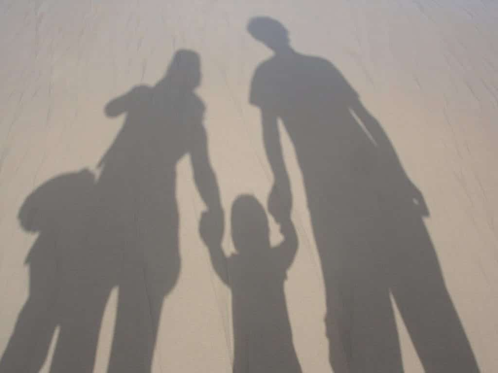Shadow of parents holding hand with child