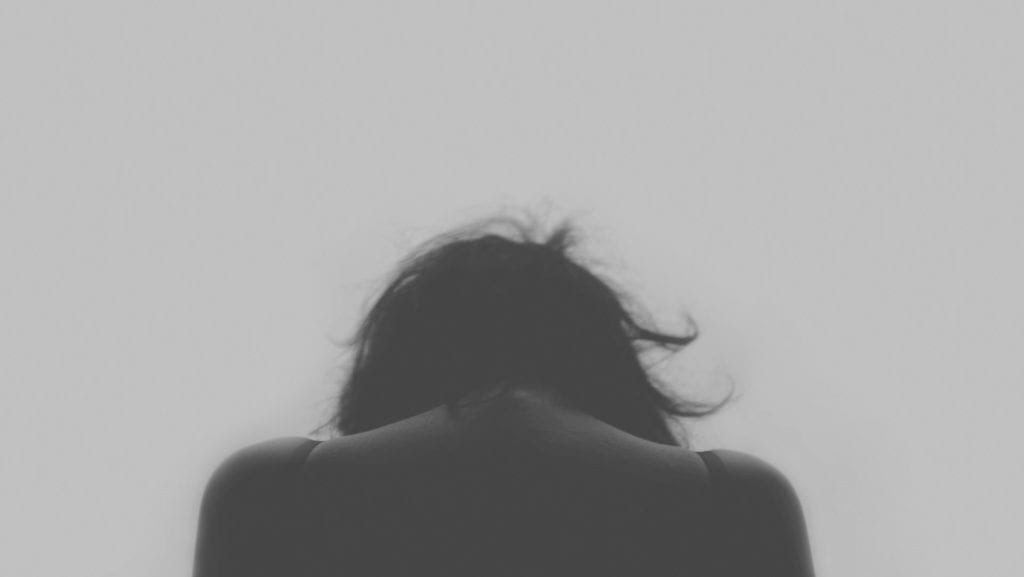 Black and white photo of woman with head down