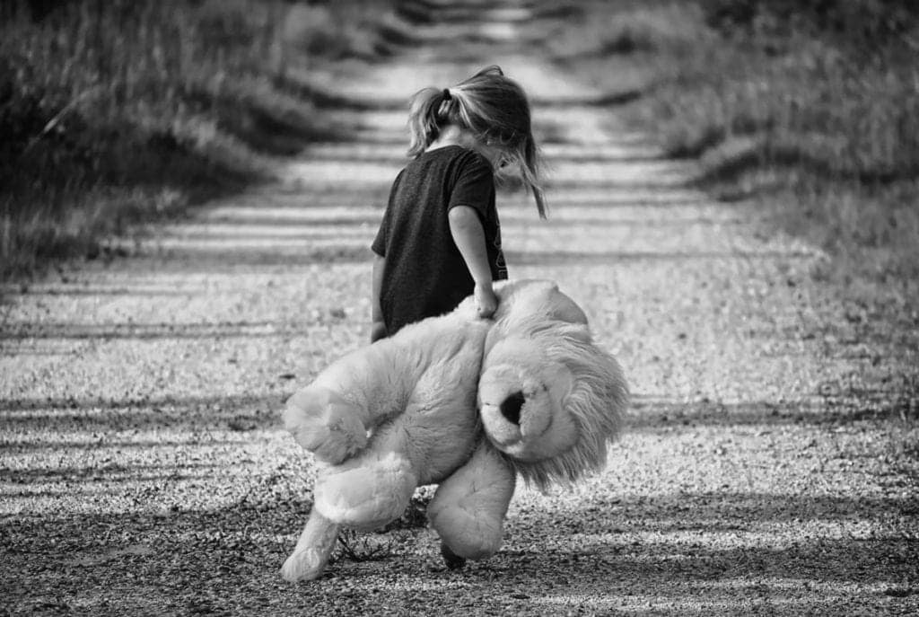 Black & White picture of child walking down road with stuffed toy