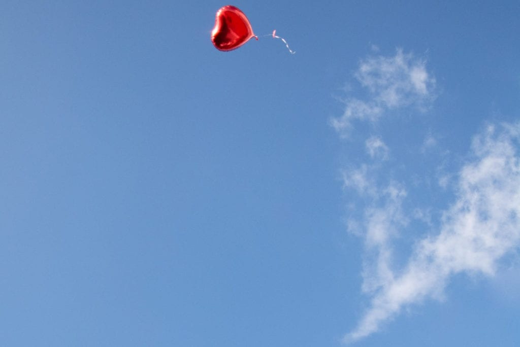 Heart ballon floating into the sky