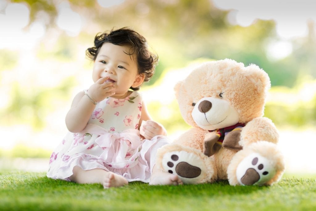 Child sitting on grass with teddy bear