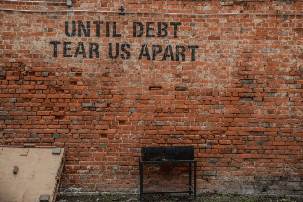 Until debt tear us apart written on a brick wall